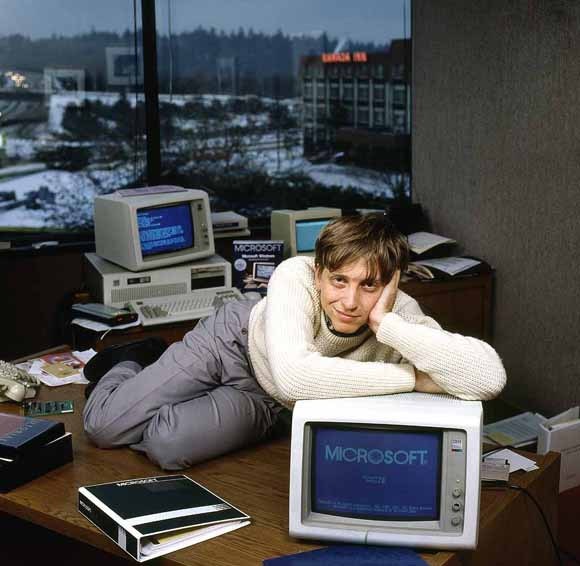 Bill Gates posing on table 80s